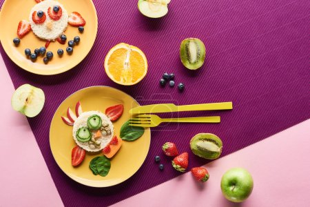 Photo for Top view of plates with fancy animals made of food near fruits on purple background - Royalty Free Image