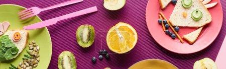 Photo pour Vue de dessus des assiettes avec des animaux de fantaisie faits de nourriture près des fruits sur fond violet, vue panoramique - image libre de droit
