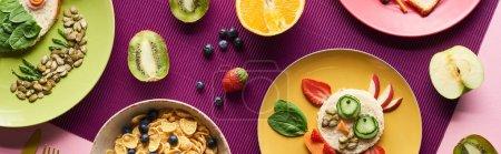 Photo pour Vue de dessus des assiettes avec des animaux de fantaisie faits de nourriture près des fruits et des céréales pour petit déjeuner sur fond violet, vue panoramique - image libre de droit
