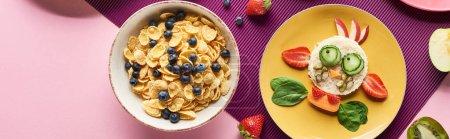 Photo pour Vue de dessus des assiettes avec vache de fantaisie faite de nourriture près de fruits et céréales de petit déjeuner sur fond violet - image libre de droit