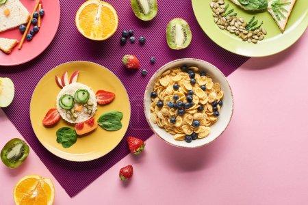 Photo pour Vue de dessus des assiettes avec des animaux de fantaisie faits de nourriture près des fruits et des céréales pour petit déjeuner sur fond violet - image libre de droit