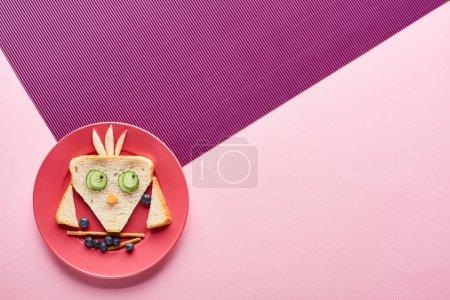 Photo pour Vue de dessus de la plaque avec oiseau de fantaisie faite de nourriture sur fond rose et violet - image libre de droit