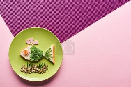 Photo pour Vue supérieure de l'assiette avec le poisson de fantaisie fait de la nourriture sur le fond rose et pourpre - image libre de droit
