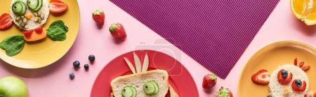Photo pour Vue de dessus des assiettes avec des animaux de fantaisie faits de nourriture sur fond rose et violet avec des fruits, vue panoramique - image libre de droit