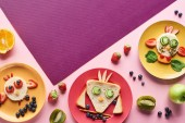 top view of plates with fancy animals made of food on pink and purple background with fruits