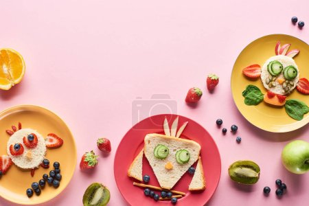 Photo pour Vue de dessus des assiettes avec des animaux de fantaisie faits de nourriture sur fond rose avec des fruits - image libre de droit