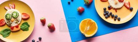 Photo pour Vue de dessus des assiettes avec des animaux de fantaisie faits de nourriture sur fond bleu et rose avec des fruits, vue panoramique - image libre de droit