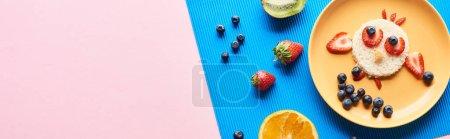 Photo pour Vue de dessus de la plaque avec un animal de fantaisie fait de nourriture sur fond bleu et rose - image libre de droit