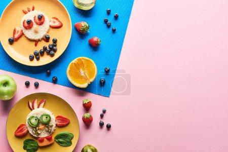 Photo pour Vue de dessus des assiettes avec des animaux de fantaisie faits de nourriture sur fond bleu et rose avec des fruits - image libre de droit