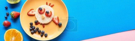 Photo pour Vue de dessus de la plaque avec un animal de fantaisie fait de nourriture sur fond bleu et rose, vue panoramique - image libre de droit