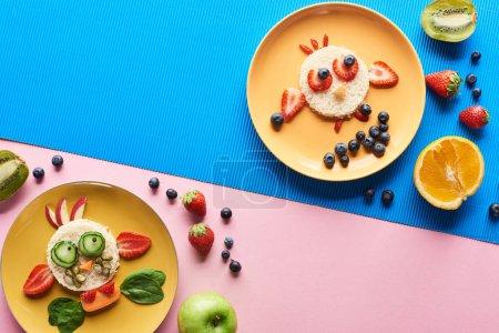 Photo pour Vue de dessus des assiettes avec des animaux de fantaisie faits de nourriture sur fond bleu et rose - image libre de droit