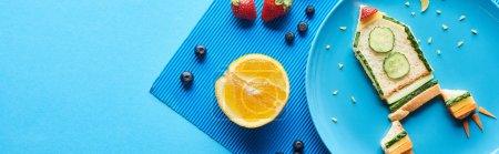 Photo pour Vue supérieure des plaques avec la fusée de fantaisie faite de la nourriture sur le fond bleu avec des fruits, projectile panoramique - image libre de droit