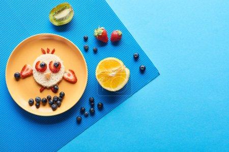 Photo pour Vue de dessus de la plaque avec animal de fantaisie fait de nourriture sur fond bleu - image libre de droit
