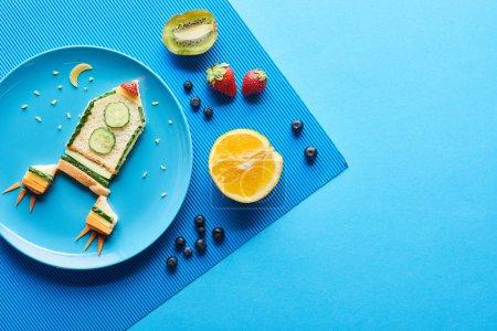 Photo pour Vue supérieure des plats avec la fusée de fantaisie faite de la nourriture sur le fond bleu avec des fruits - image libre de droit