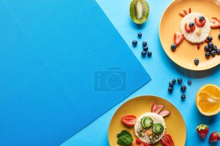 Photo pour Vue de dessus des assiettes avec des animaux de fantaisie faits de nourriture sur fond bleu - image libre de droit