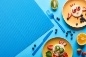 top view of plates with fancy animals made of food on blue background