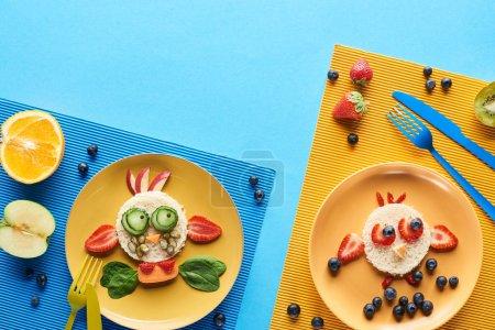 Photo pour Vue de dessus des assiettes avec des animaux de fantaisie faits de nourriture sur fond bleu et jaune - image libre de droit