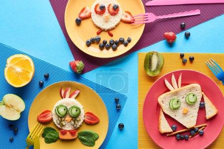 Photo pour Vue supérieure des plats avec des animaux de fantaisie faits de nourriture sur le fond bleu et jaune - image libre de droit