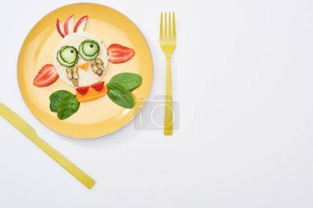 Photo pour Vue de dessus de l'assiette avec animal de fantaisie fait de nourriture pour le petit déjeuner des enfants près de couverts sur fond blanc - image libre de droit