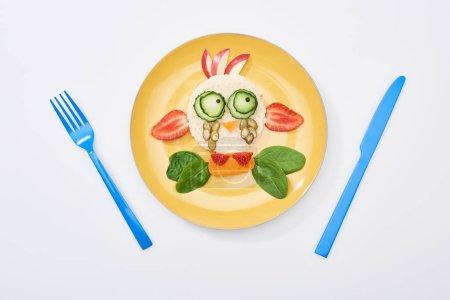 Photo pour Vue du dessus de l'assiette avec vache de fantaisie faite de nourriture pour le petit déjeuner des enfants près de couverts sur fond blanc - image libre de droit