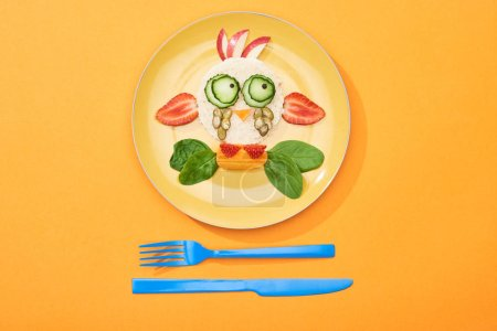 Photo pour Vue du dessus de l'assiette avec vache de fantaisie faite de nourriture pour le petit déjeuner des enfants près de couverts sur fond orange - image libre de droit