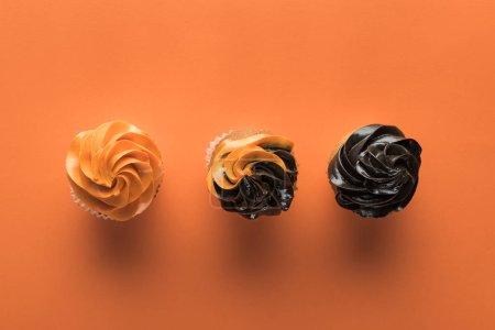 Foto de Vista superior de deliciosos cupcakes de Halloween sobre fondo naranja - Imagen libre de derechos
