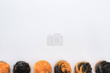 top view of Halloween cupcakes on white background with copy space