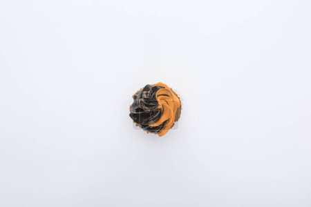top view of delicious Halloween black and orange cupcake isolated on white
