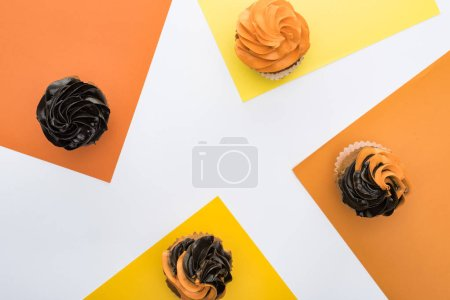 Photo for Top view of delicious Halloween cupcakes on orange, yellow and white background with copy space - Royalty Free Image