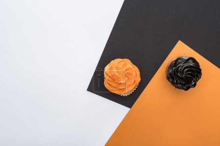 top view of delicious Halloween cupcakes on black, orange and white background with copy space