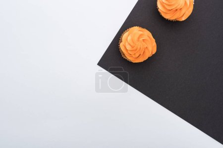 Photo for Top view of delicious Halloween cupcakes on black and white background with copy space - Royalty Free Image
