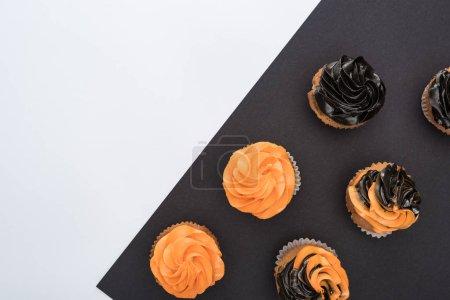 Draufsicht auf köstliche Halloween-Cupcakes auf schwarz-weißem Hintergrund mit Kopierfläche