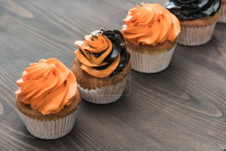 Photo for Delicious Halloween black and orange cupcakes on wooden table - Royalty Free Image