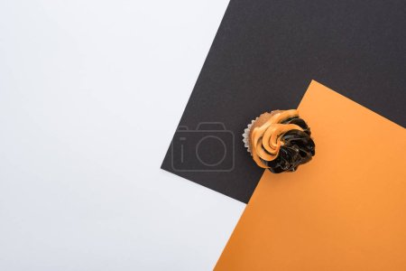 Photo for Top view of delicious Halloween cupcake on orange, black and white background with copy space - Royalty Free Image