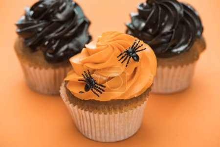 Photo for Selective focus of delicious Halloween cupcakes with spiders on orange background - Royalty Free Image