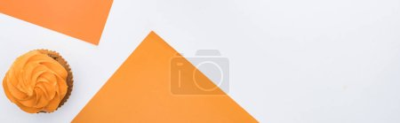 top view of delicious Halloween cupcake on orange and white background with copy space, panoramic shot