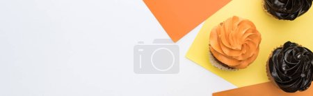 top view of delicious Halloween cupcakes on yellow, orange and white background with copy space, panoramic shot