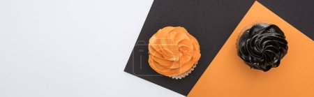 top view of delicious Halloween cupcakes on black, orange and white background with copy space, panoramic shot