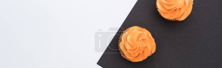 Photo for Top view of delicious Halloween cupcakes on black and white background with copy space, panoramic shot - Royalty Free Image