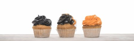 delicious Halloween orange and black cupcakes isolated on white, panoramic shot