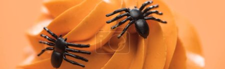 close up view of spooky Halloween cupcake with spiders on cream isolated on orange, panoramic shot