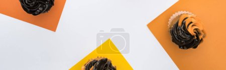 Photo for Top view of delicious Halloween cupcakes on yellow, orange and white background, panoramic shot - Royalty Free Image