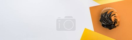 Photo for Top view of delicious Halloween cupcake on yellow, orange and white background with copy space, panoramic shot - Royalty Free Image