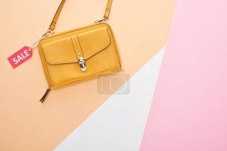 Photo pour Vue du haut du sac avec étiquette de vente sur fond beige, blanc et rose - image libre de droit