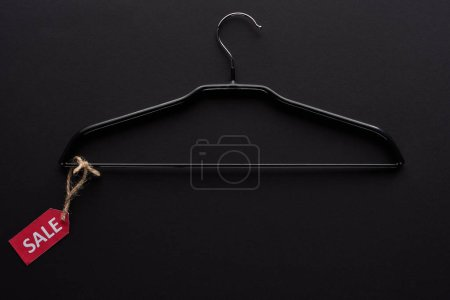 Photo for Top view of hanger with sale label on black background - Royalty Free Image