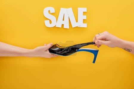 Photo pour Vue recadrée de femmes tenant chaussure en vente lettrage sur fond jaune - image libre de droit