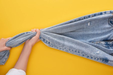 Photo for Top view of woman pulling jeans on yellow background - Royalty Free Image