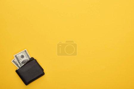 vista superior de la billetera con billetes de dólar sobre fondo amarillo