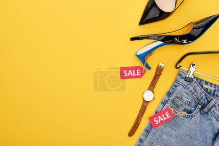 Photo pour Vue du haut des vêtements à la mode avec étiquette de vente sur fond jaune - image libre de droit