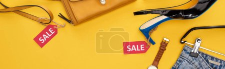 Photo pour Top view of fashionable clothing with sale labels on yellow background, panoramic shot - image libre de droit
